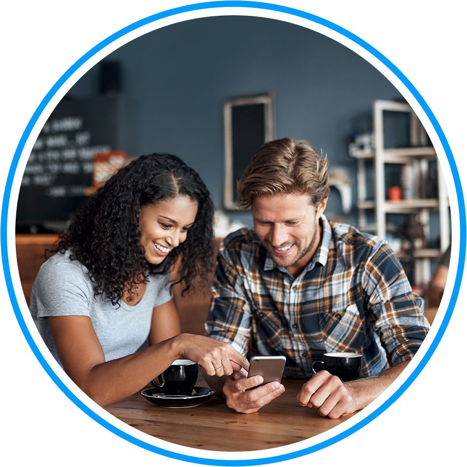 Circular image of a couple sat in a cafe, scrolling through an app on a shared mobile phone
