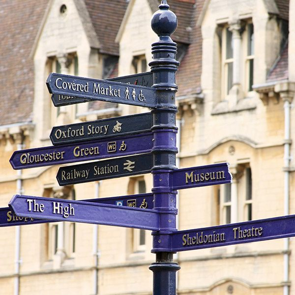 """Blue street sign in Oxford, England with many directions in front of classing Oxford architecture."""