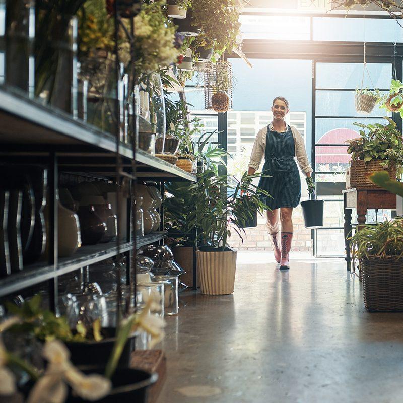 A Female garden centre employee caries plants through a shop aisle